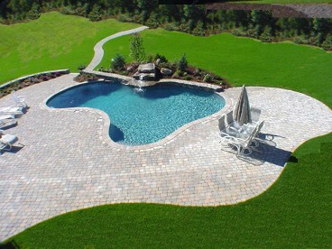 Free form pool with waterfall, sitting wall and paver deck