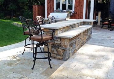 Bi level stone bar with blue stone top and built in grill by New View