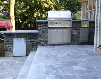 Stone bar on travertine patio steps with built in grill, refrigerator and side burner.