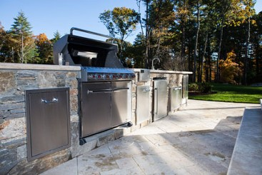 Stone bar with built in Grill, refrigerator, trash center and side burners