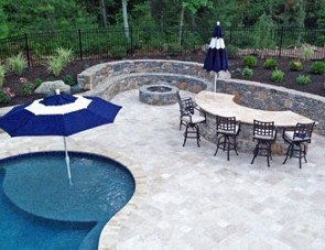 Stone bar with tavertine patio, sitting wall with fire pit  and pool with tanning shelf by New View