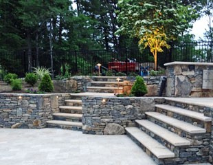 Sunken Travertine patio and stone steps by New View