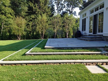 Stone patio with sod and travertine steps by New View