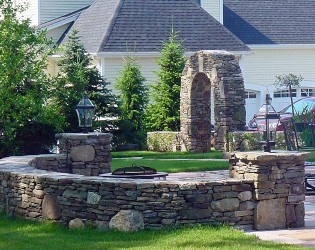 Stone sitting walls with light posts and stone arch by New View