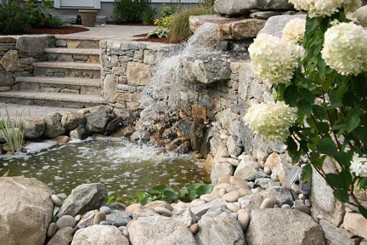 Natural pond with waterfall and stone steps to fire pit