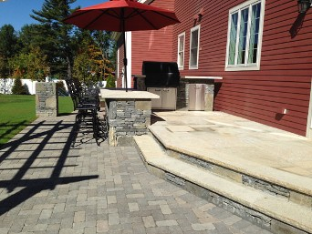 Stone bar, built into patio steps with travertine top by New View