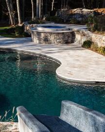 Hot tub with travertine patio, free form pool and slide by New View