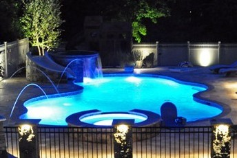 Pool and spa with night lights, fountains and slide by New View