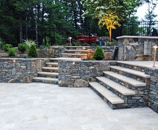 Multi-level Travertine patio with retaining walls and steps by New View