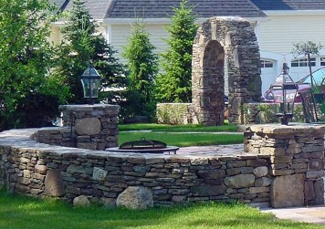 Stone wall with posts and Arched garden entrance by New View