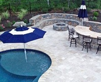 Fire pit with sitting wall, stone bar and pool with wading shelf by New View