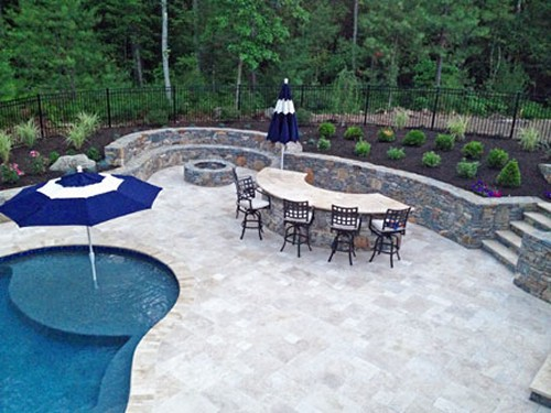 Stone Bar with Tavertine Patio, Sitting Wall with Fire Pit& Pool with Tanning Shelf by New View