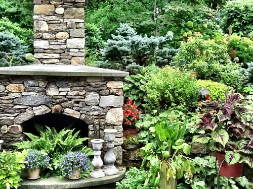 Fieldstone Fireplace with Angled Blue Stone Mantle, Raised Hearth with Arched Opening, and Landscape by New View